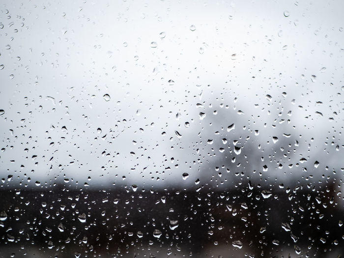 Water Drops on a window with grey skies and silhouettes of houses in background Drop Wet Water Rain Glass - Material Transparent No People Window Sky Nature Full Frame RainDrop Indoors  Rainy Season Day Close-up Backgrounds Glass