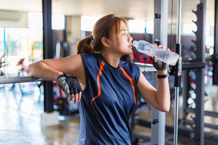 Young Asian woman taking a rest to drink water during her gym work out Asian  Excercising Working Out Bottle Drink Exercising Food And Drink Gym Holding Lifestyles One Person Refreshment Sports Clothing Water Bottle  Women Young Women
