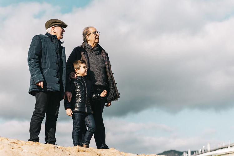 Full length of senior men with child standing against sky