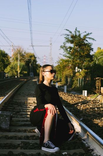 Young Woman Looking Away While Sitting On Railroad Track