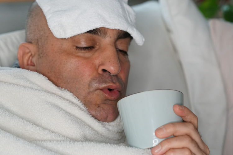 Man Suffering From Headache Having Coffee On Bed At Home