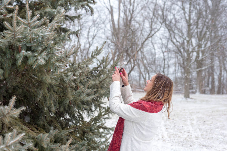 Woman with christmas tree in snow