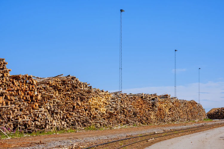 Stack of logs on road against clear blue sky