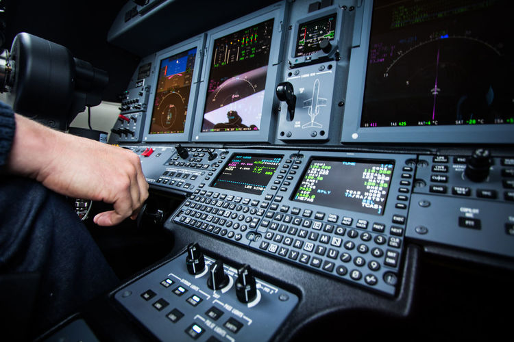Cropped image of man using laptop at airplane