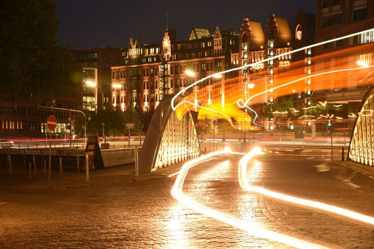 Light trails on bridge over river at night