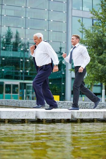 Full Length Of Businessmen Running On Footbridge Over Lake