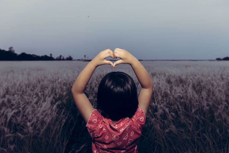 Rear view of girl making heart shape while standing on land against clear sky