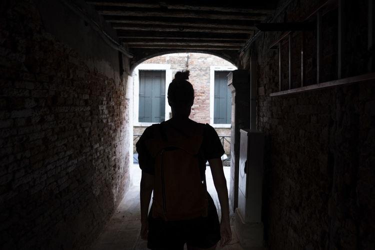 In silhouette woman walking in tunnel in building