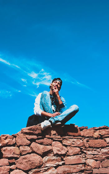 Low angle view of smiling young man sitting on stone wall against blue sky