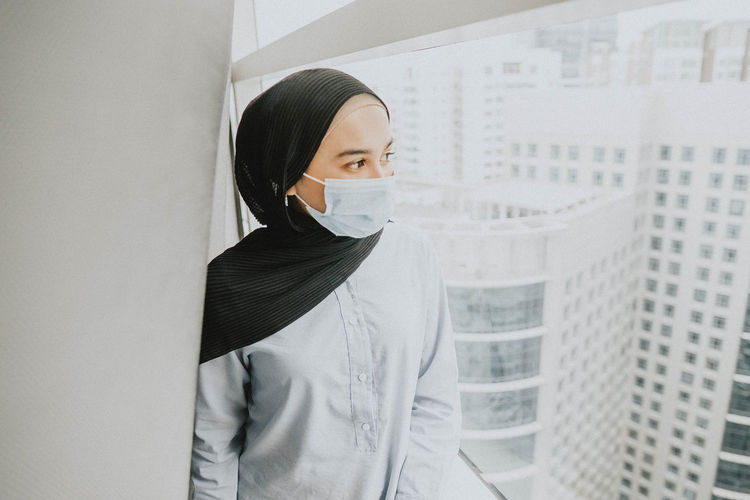 Portrait of young woman wearing facemask standing against wall
