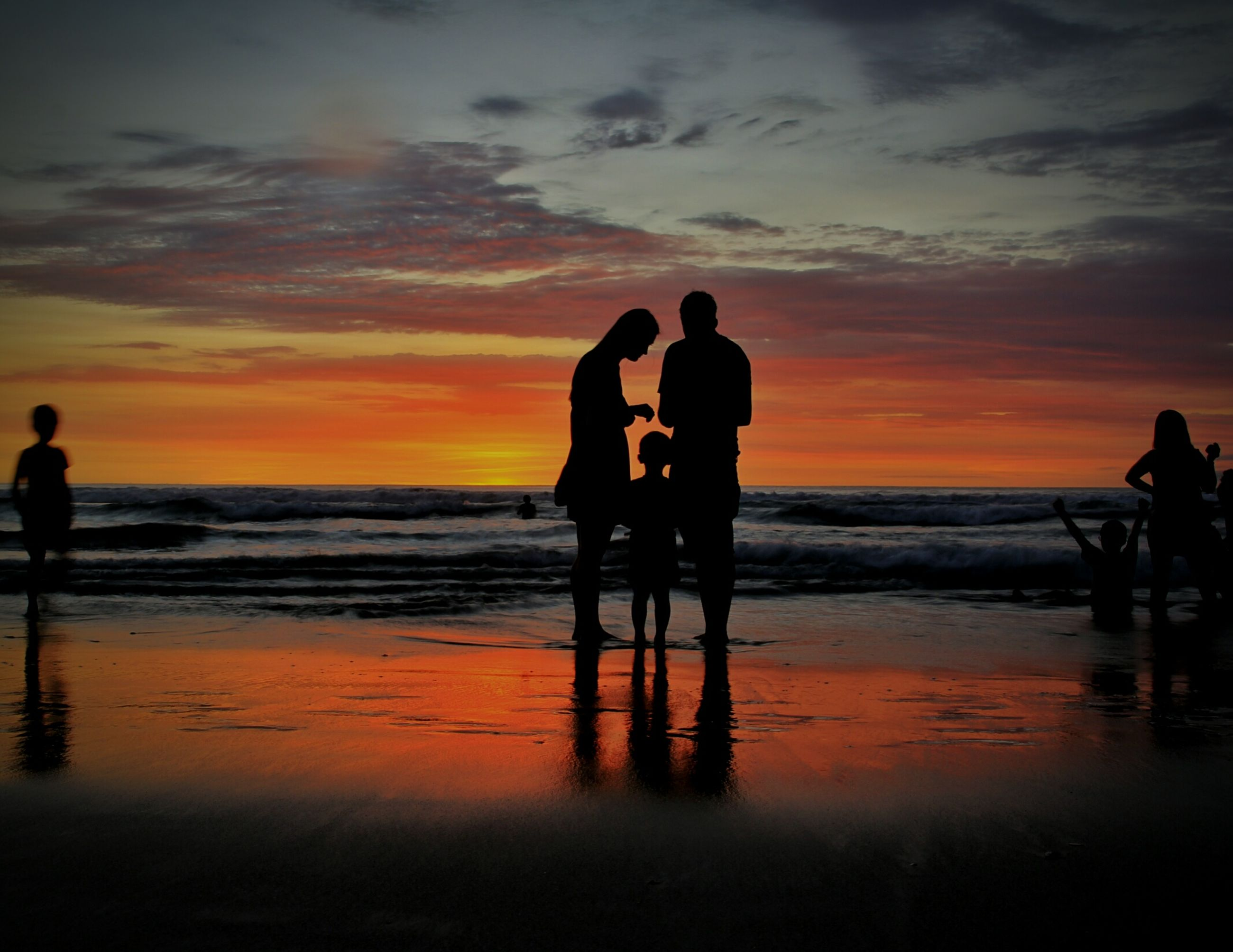 sunset, sea, water, silhouette, horizon over water, beach, orange color, sky, leisure activity, lifestyles, shore, men, scenics, standing, beauty in nature, vacations, tranquil scene, reflection