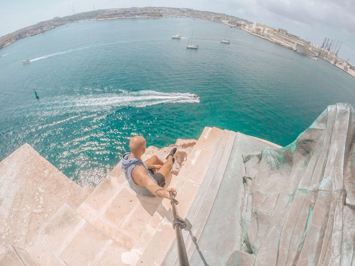 High angle view of man holding monopod while sitting on rock formation against sea