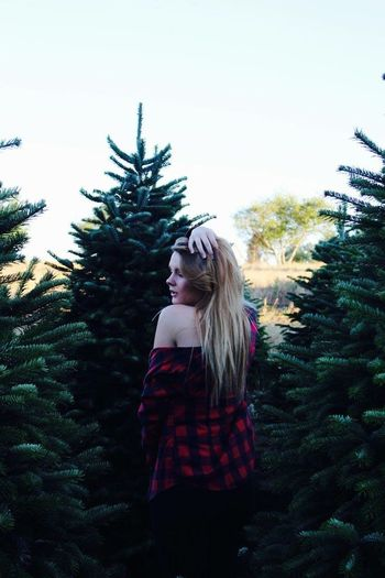 Rear View Of Young Woman With Hand In Hair Standing Against Pine Trees