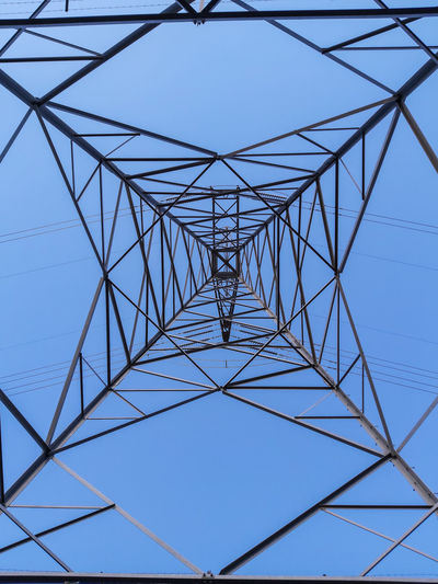 Low angle view of electricity pylon against clear sky
