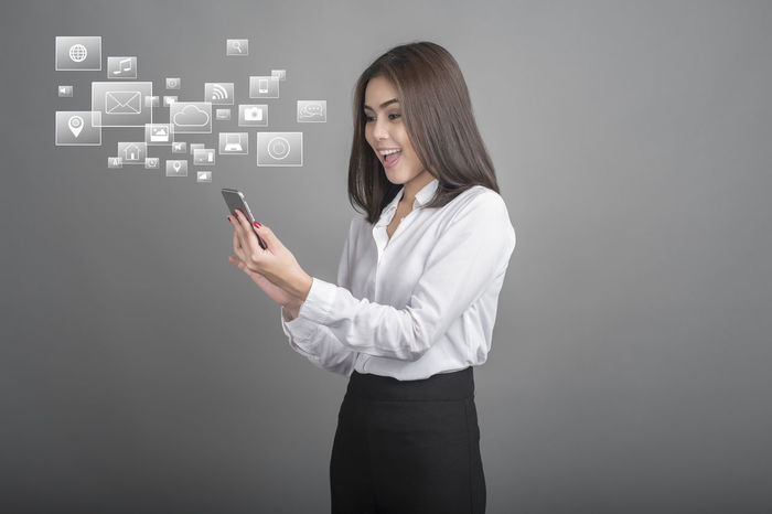Beautiful Woman Business Business Businesswoman Chats Communication Connection Finance Global Communications Globalization Gray Background Holding Internet Mobile Phone One Person Portable Information Device Smart Phone Smiling Standing Talking Photo Tech Technology Touch Screen Wireless Technology Young Adult
