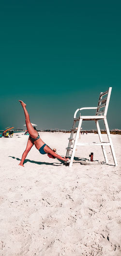 Low angle view of young woman stretching on beach