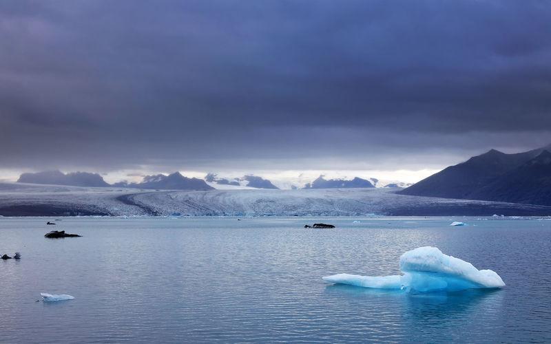 Scenic view of iceberg in lagoon against sky