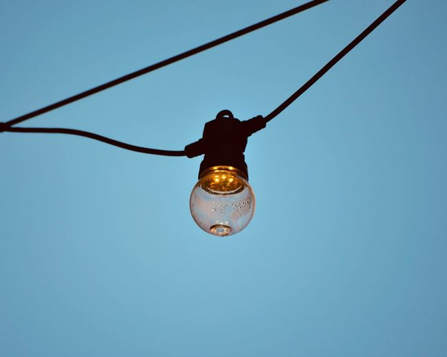 Low angle view of light bulb hanging on cable against sky