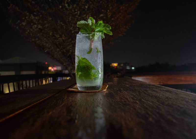 Table Alcohol Drink Glass Cocktail Drinking Glass Food And Drink Refreshment Household Equipment Night Bar - Drink Establishment Wood - Material No People Freshness Cold Temperature Focus On Foreground Water Leaf Nature Mojito Bar Counter Rum Rooftops Backlighting City Life