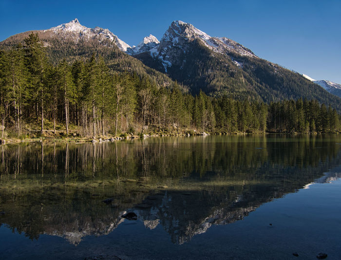 The partly still snow-covered mountains are reflected in the mountain lake. Hintersee Germany Berchtesgaden Lake Mountain Lake Stones Ramsau  Springtime Beautiful Nature National Park