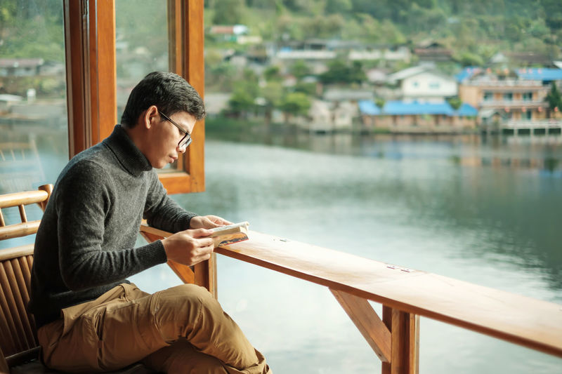 Man reading book while sitting on chair against lake