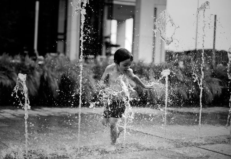 fountain Motion Water One Person Splashing Child Day Fun Childhood Nature Enjoyment Lifestyles Real People Leisure Activity Wet Architecture Outdoors Refreshment Playing Kids Being Kids Kidsphotography Foutain City Life Streetphotography Blackandwhite Fun