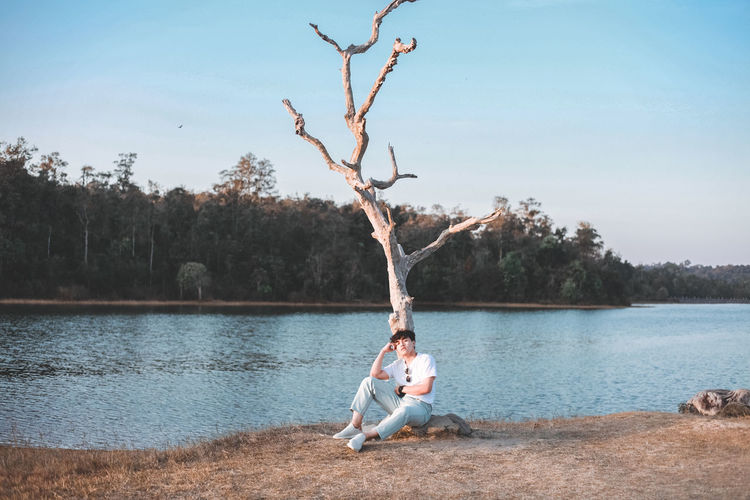 Man sitting by lake against sky