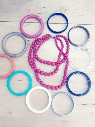 High angle view of colorful bangles with necklace on table