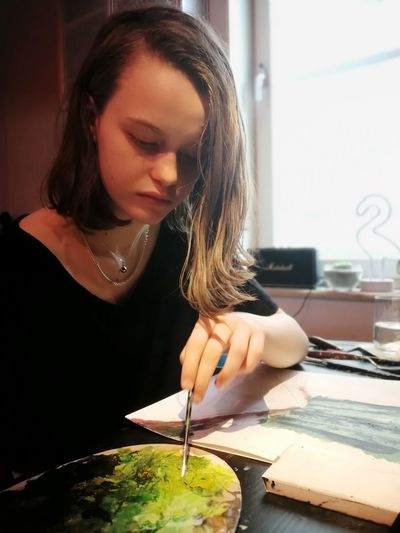 Teenage Girl Making Painting On Table At Home