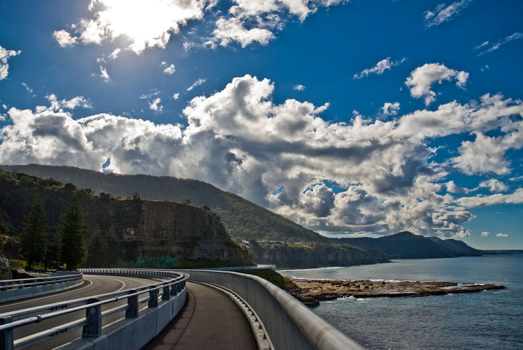 Panoramic view of road by sea against sky