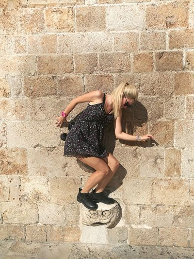 Full Length Of Young Woman Balancing Against Wall