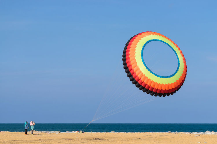 Low angle view of large colorful kite flying over beach against clear blue sky