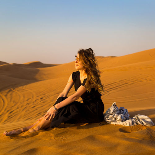 Beautiful woman sitting on sand in desert