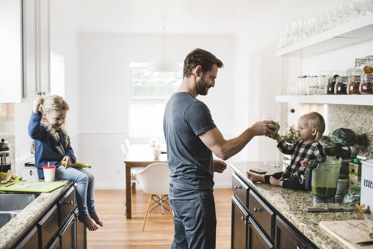 Men standing on table at home
