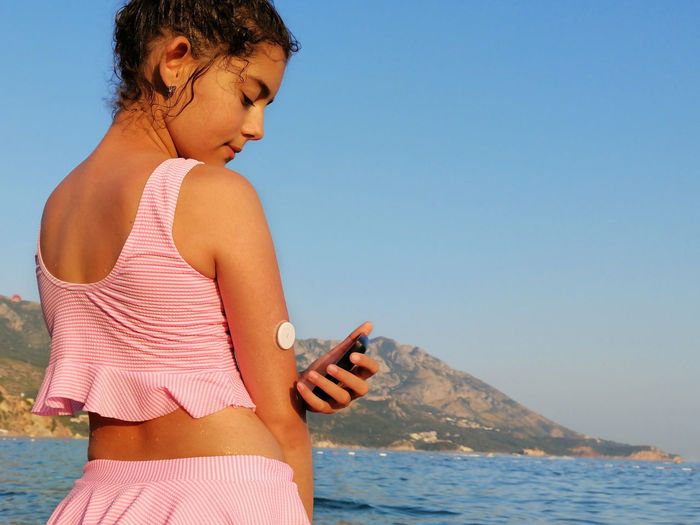 Life with diabetes. girl checks glucose level with cgm device before enters the sea.