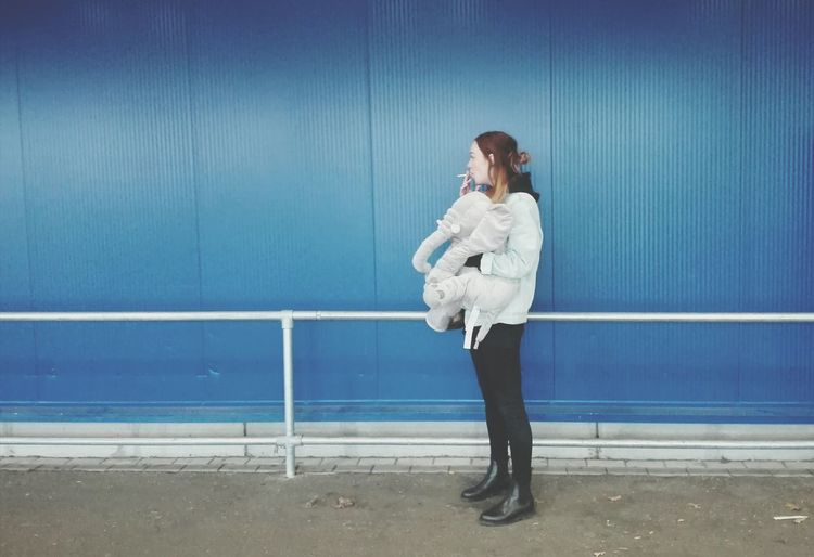 Young Woman Standing Against Blue Wall