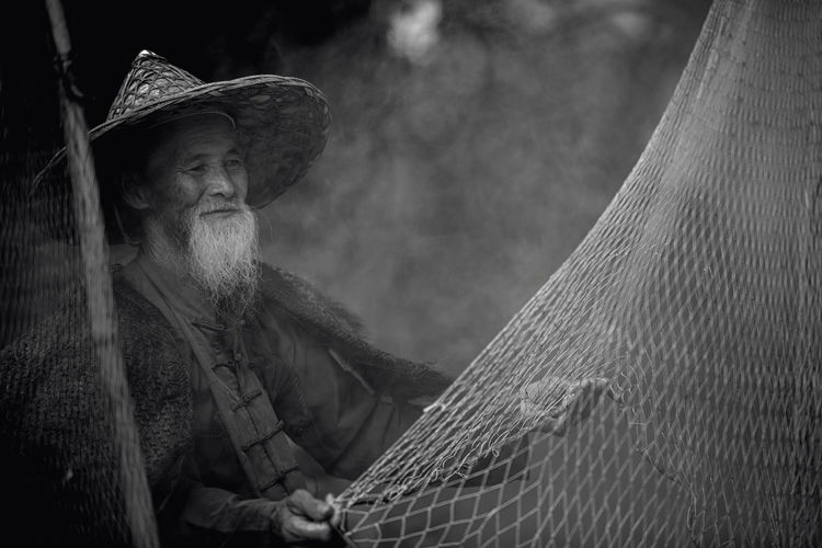 Man In Hat Looking At Fishing Net Outdoors