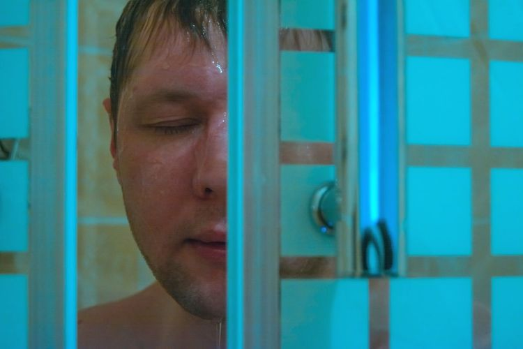 Close-up of mid adult man bathing seen through doorway