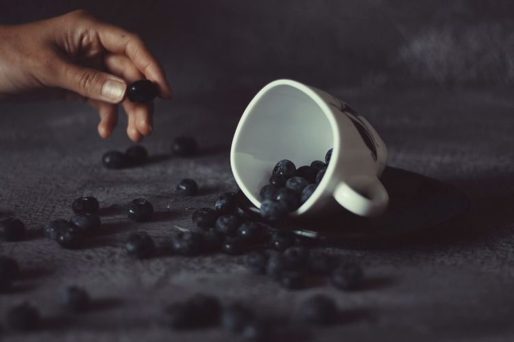 Close-Up Of Spilled Berries And Cup