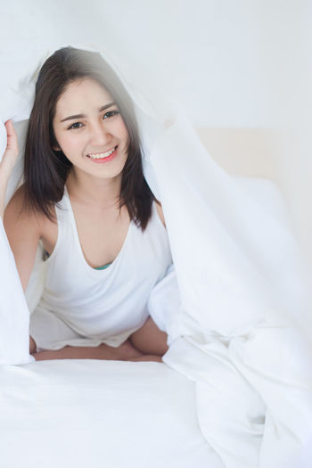 Portrait Of Smiling Beautiful Woman Lying On Bed At Home