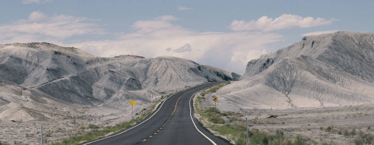 Empty road amidst mountains against sky