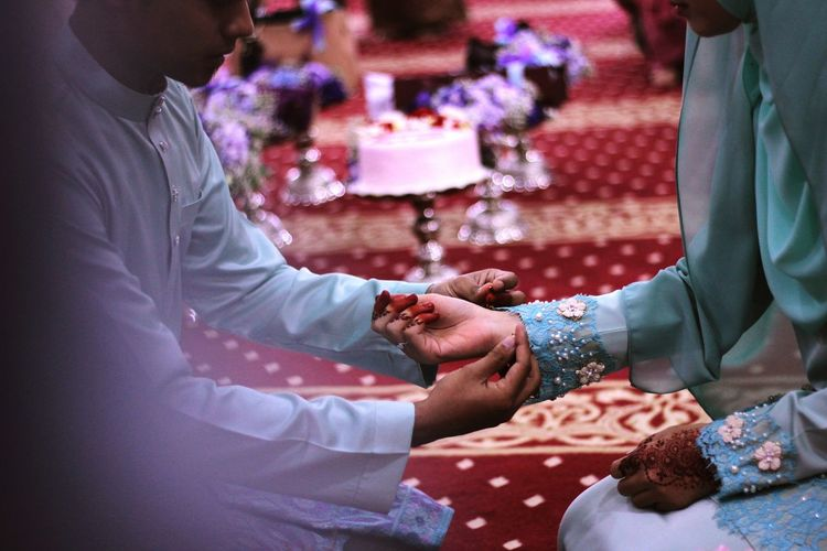 Midsection of groom tying bracelet on bride wrist during wedding ceremony