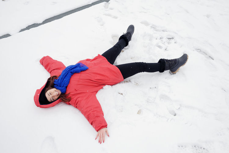 High angle view of woman making snow angel on land