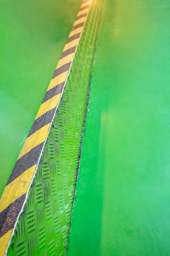 Industrial striped road or step warning on green walkway. yellow-black pattern. Construction Dark Graphic Industrial Road Sign Steps Transportation Black And Yellow  Grungy Harzard Pattern Safety Warning Sign