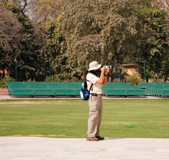 A tourist using a high powered camera inside the Red Court in New Delhi, India. In the background is a lot of grass and greenery Camera Grass Man Taking Photos Metal Bench Park - Man Made Space Park Bench Person Photographer Photography Tree