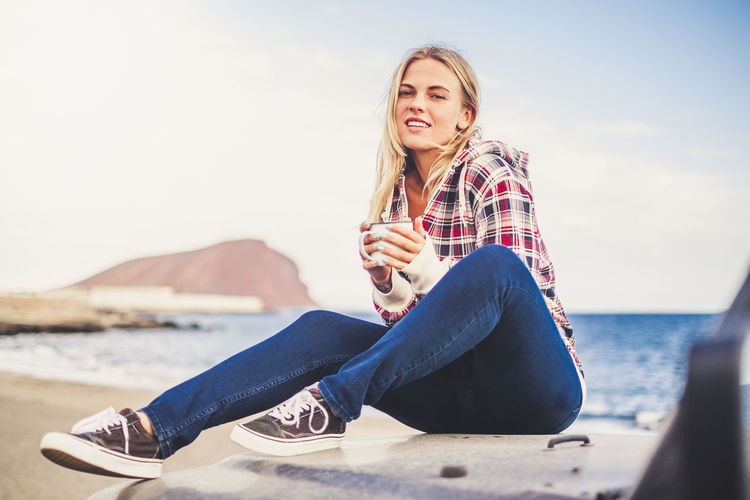 Portrait of smiling young woman holding mug while sitting on off-road vehicle against sea