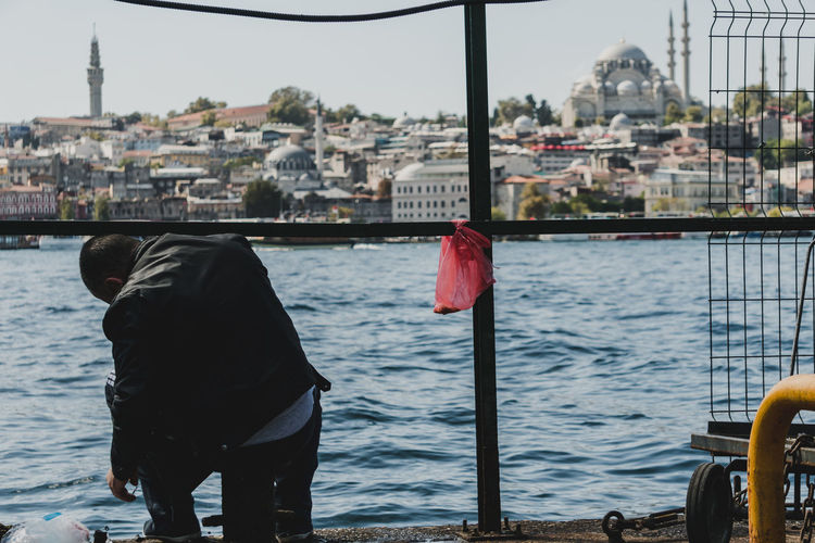 A fisherman slouches to prepare his bait near the river in Istanbul. - IG: @LostBoyMemoirs (All photos taken on Sony A6300 and edited in Lightroom). Istanbul Turkey Turkish EyeEm Best Shots The Week on EyeEm Streetwise Photography Streetphotography Street Photography People People Watching people and places Travel Water Focus On Foreground Real People City The Art Of Street Photography