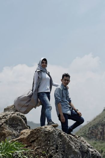 Portrait of couple standing on rock against sky