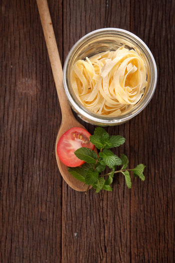Raw pasta and tomato on table