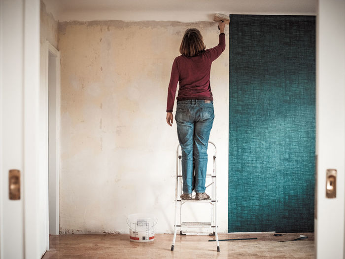 Rear view of woman painting wall while standing on step ladder at home